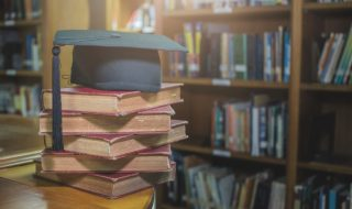 graduation cap on Books step in Library room