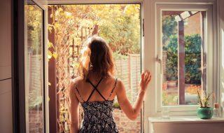 Woman standing in doorway at sunrise