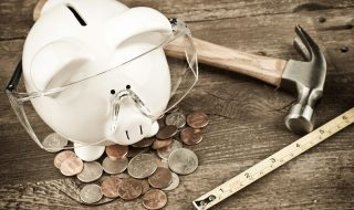 Piggy bank wearing safety goggles with hammer and tape measure on old wood background.